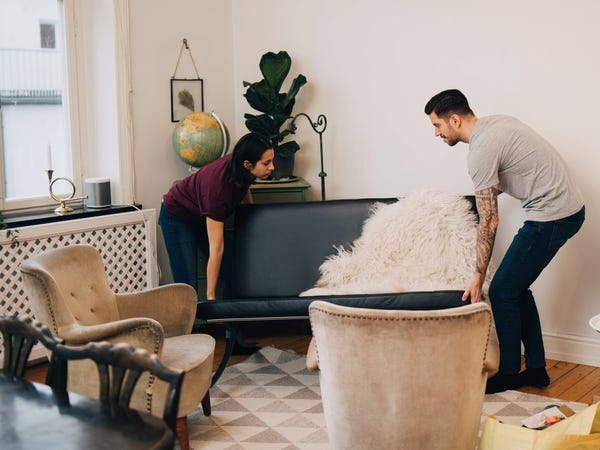 a young couple moving their couch as they rearrange their living room