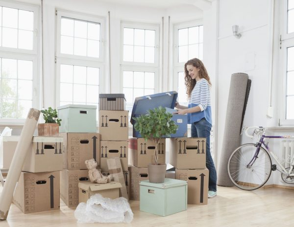 a woman in a new apartment unloading a box