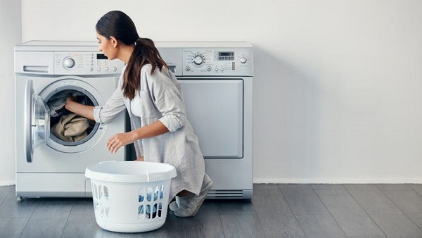 A woman loading a washer