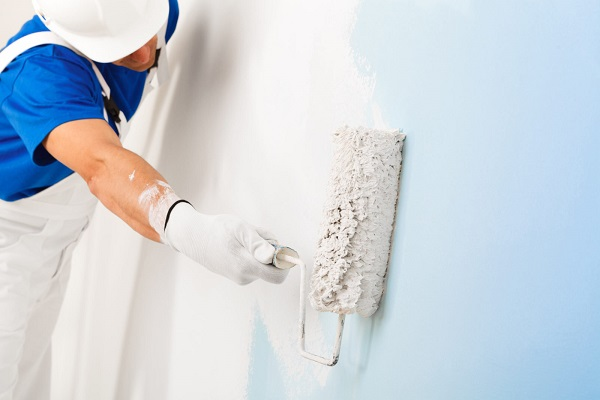 A handyman painting a wall with a paint roller